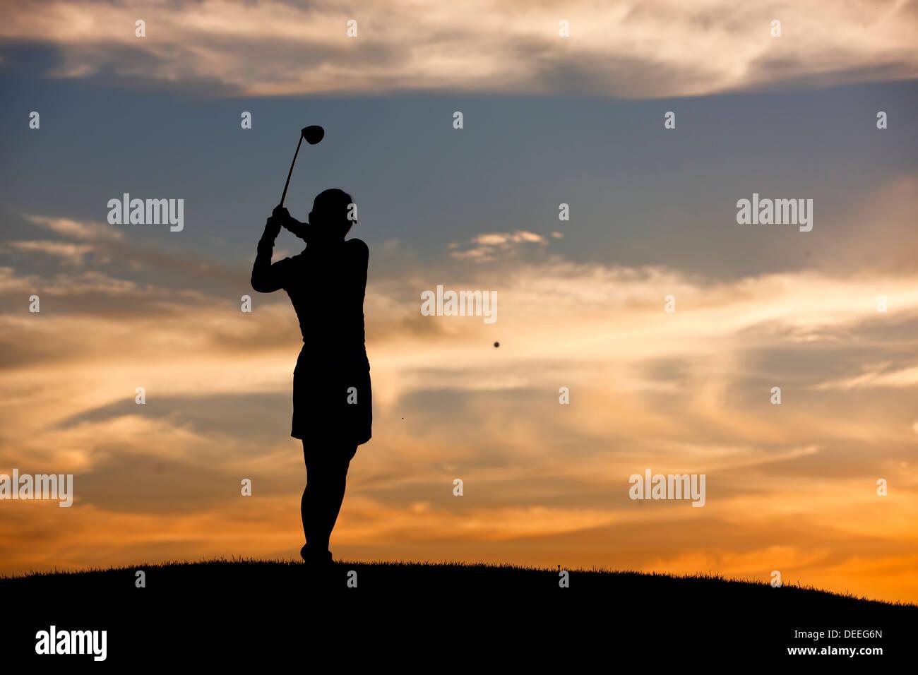 Golpear la bola de golf al atardecer. Imagen De Stock
