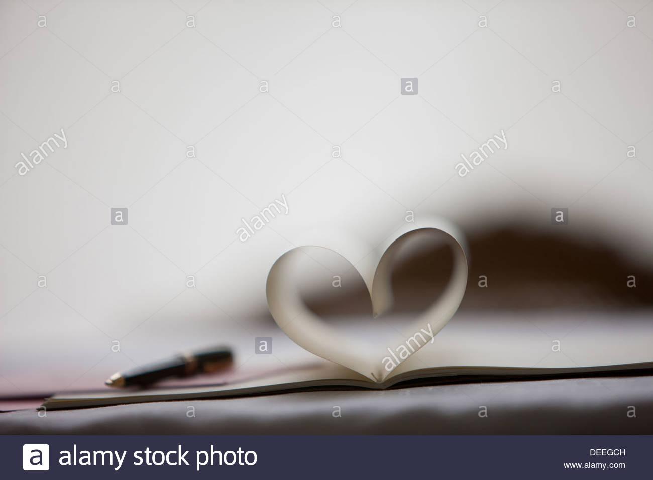 Pluma y páginas de cuaderno formando forma de corazón Imagen De Stock