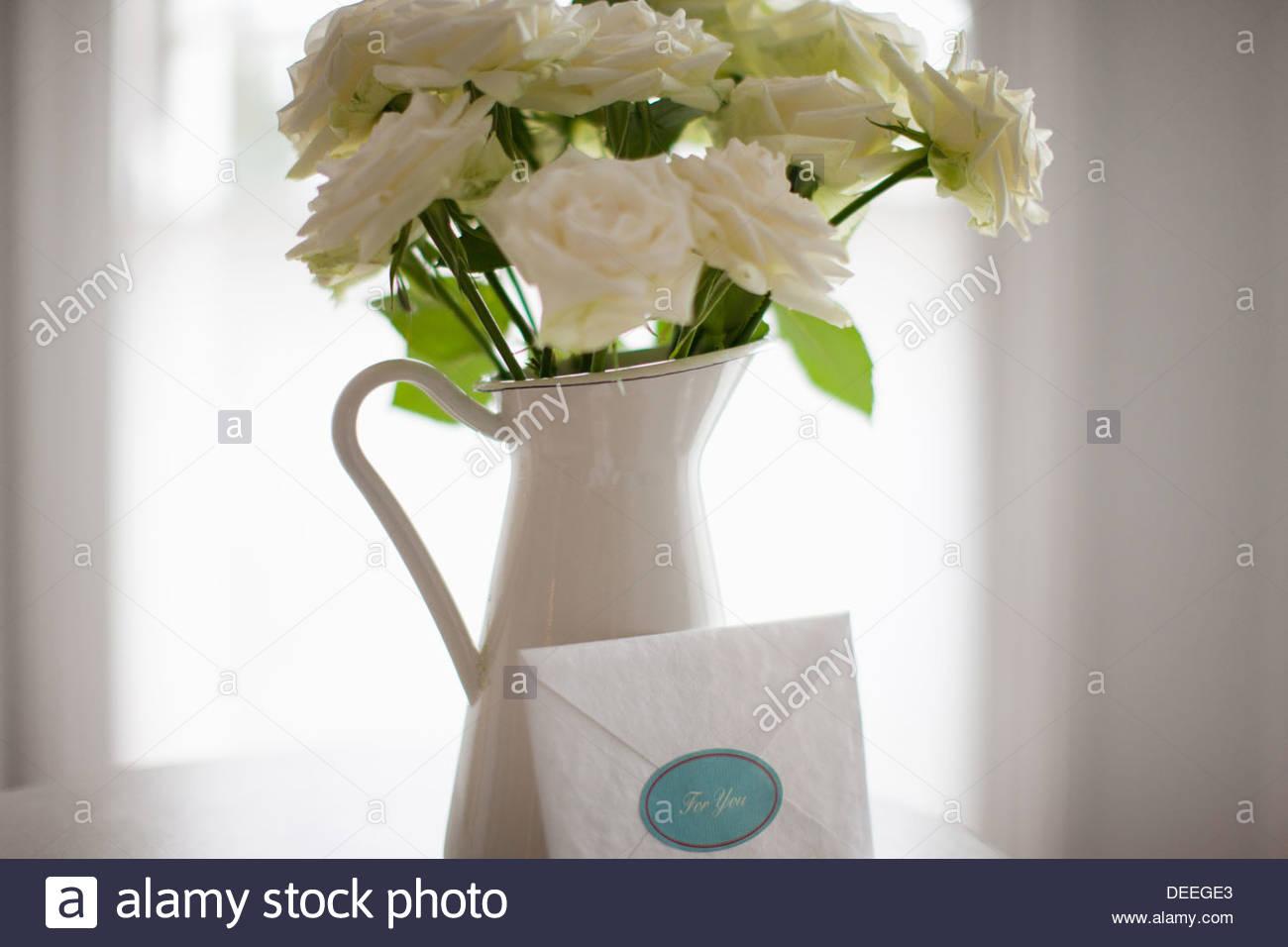 Tarjeta inclinada contra rosa blanca ramo de la lanzadora Imagen De Stock