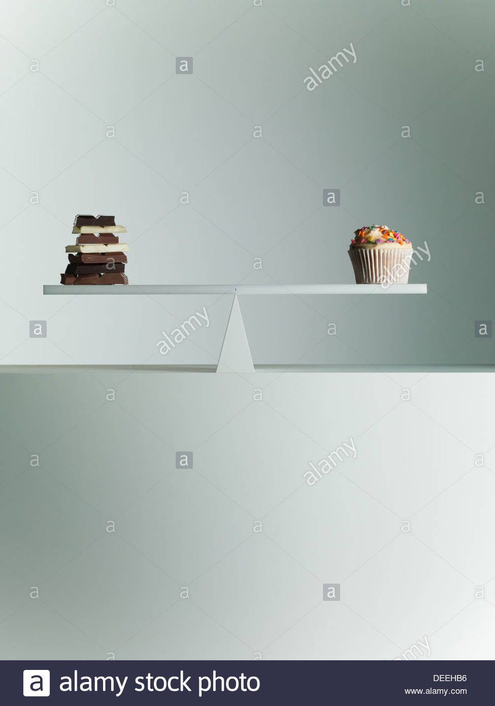 Barras de chocolate y Cupcake equilibrado a balancín Imagen De Stock