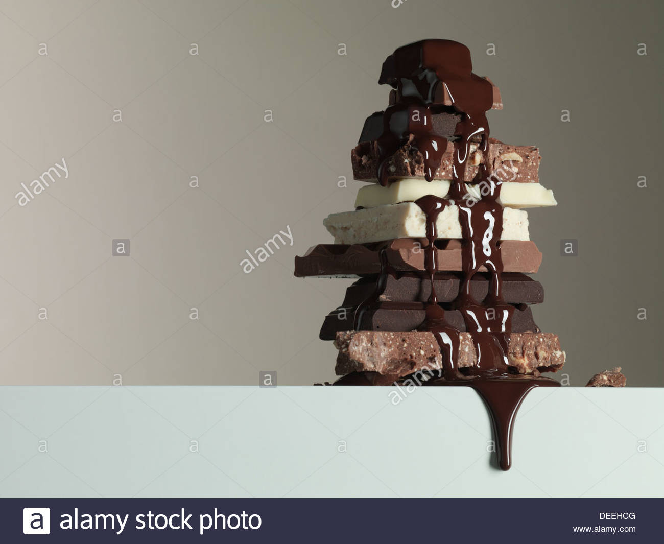 Jarabe de chocolate goteando a través de la pila de barras de chocolate Imagen De Stock