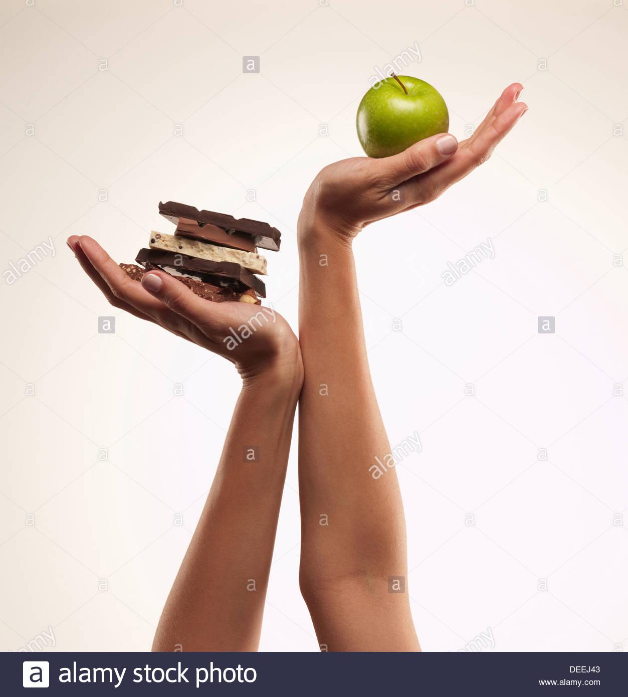 Mujer manzana verde de catación sobre barras de chocolate Imagen De Stock