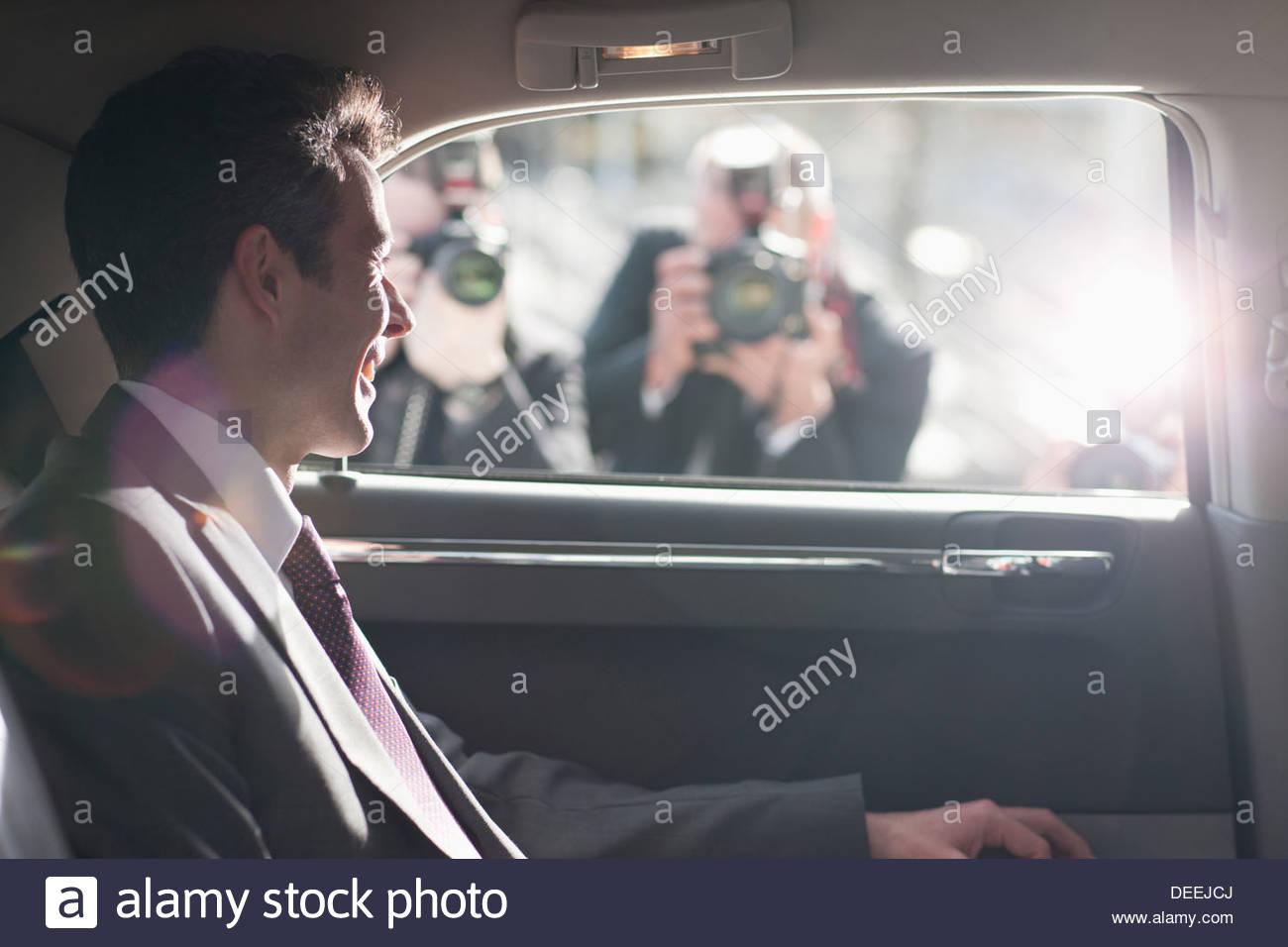 Político sonriendo a paparazzi en el backseat del coche Imagen De Stock