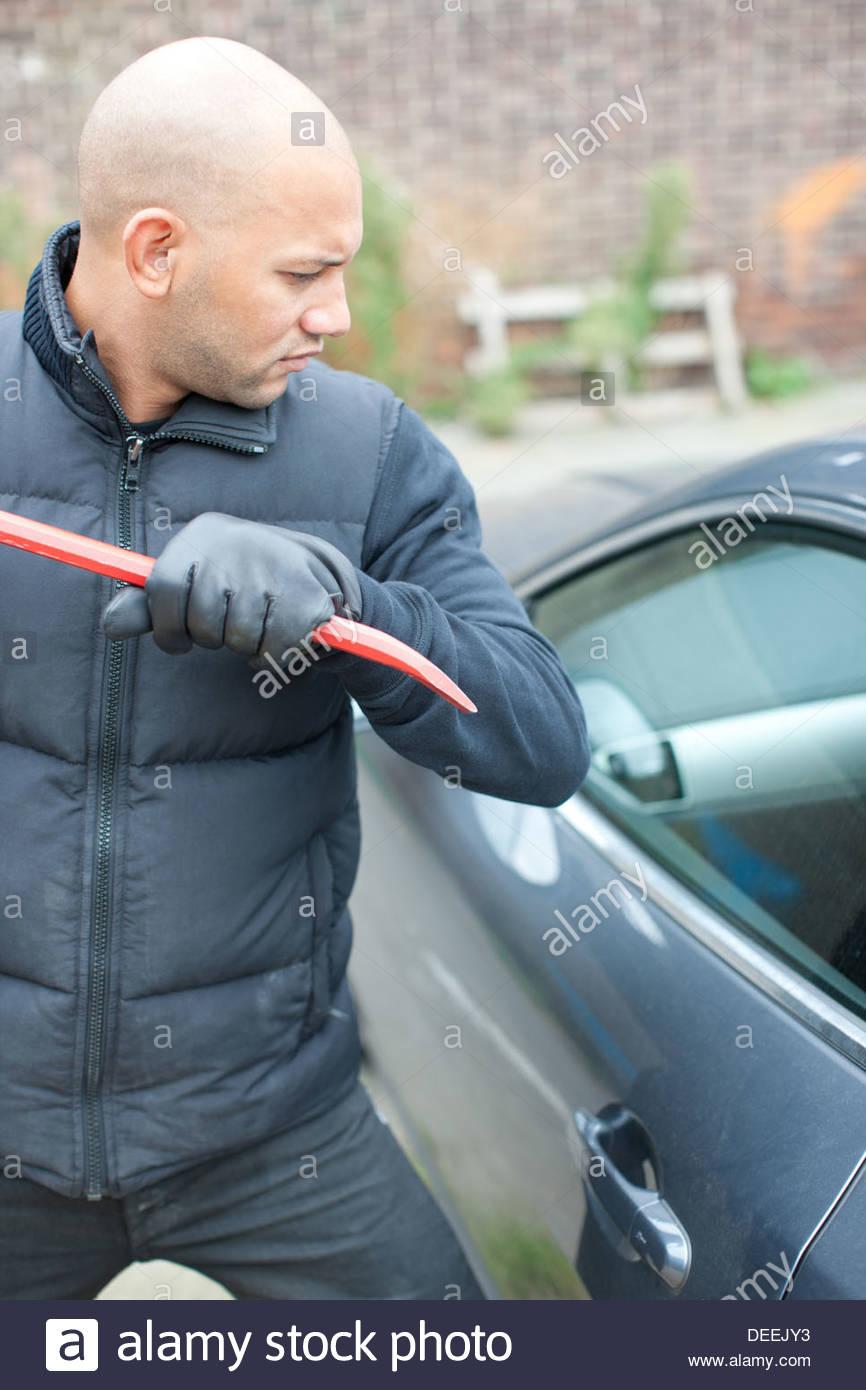 Ladrón de coche curiosos ventana abierta con una palanqueta Imagen De Stock
