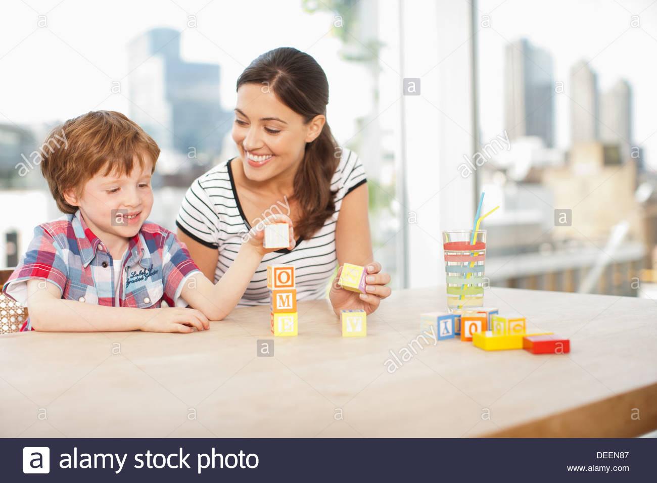 """Madre Mira hijo apilar bloques de letras y ortografía """"hogar"""" Imagen De Stock"""