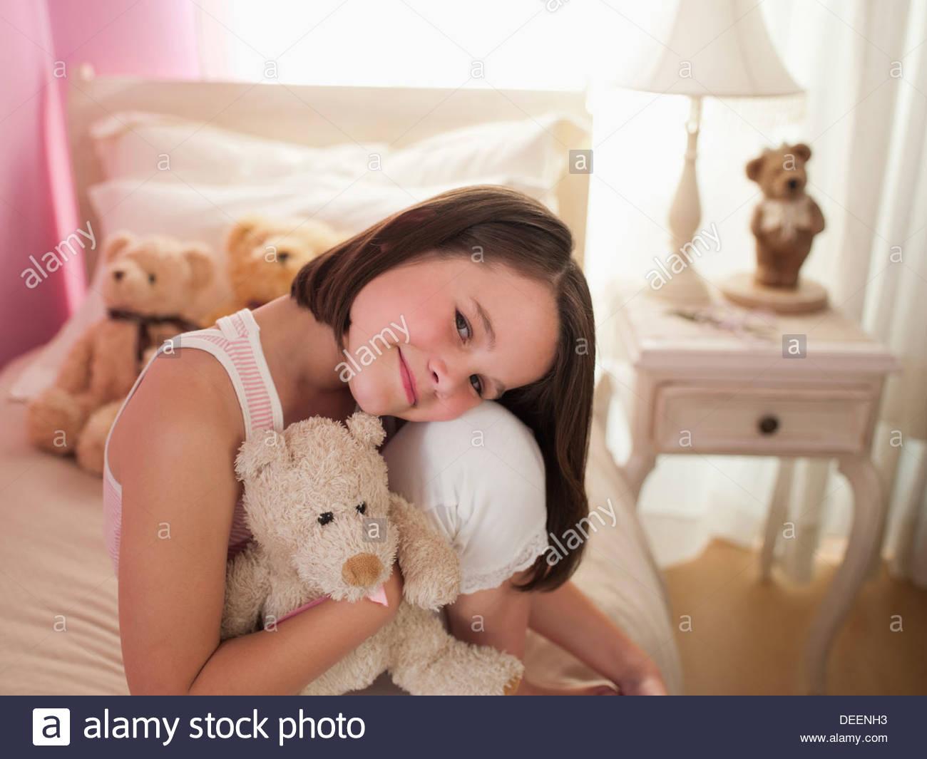 Chica abrazando el muñeco de peluche en la cama Imagen De Stock