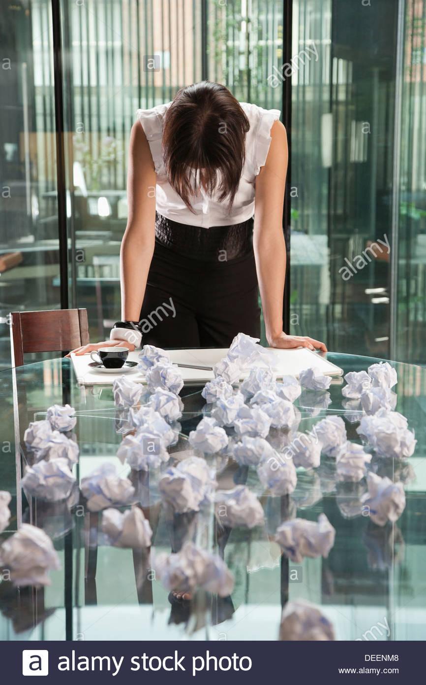 La empresaria de pie con papeles arrugados en una oficina. Imagen De Stock