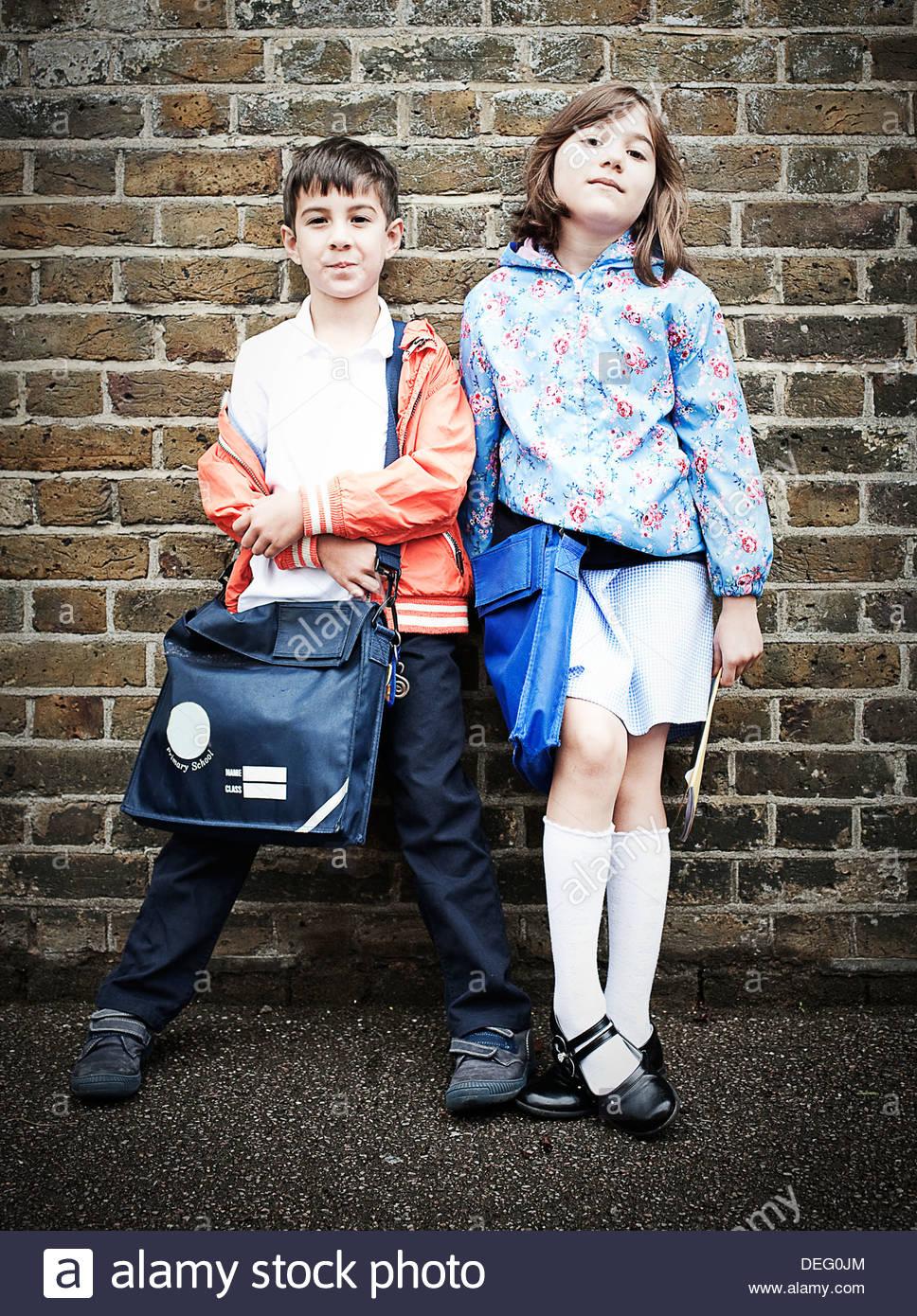 Chico y chica de pie delante de la pared de ladrillo con mochilas escolares Imagen De Stock