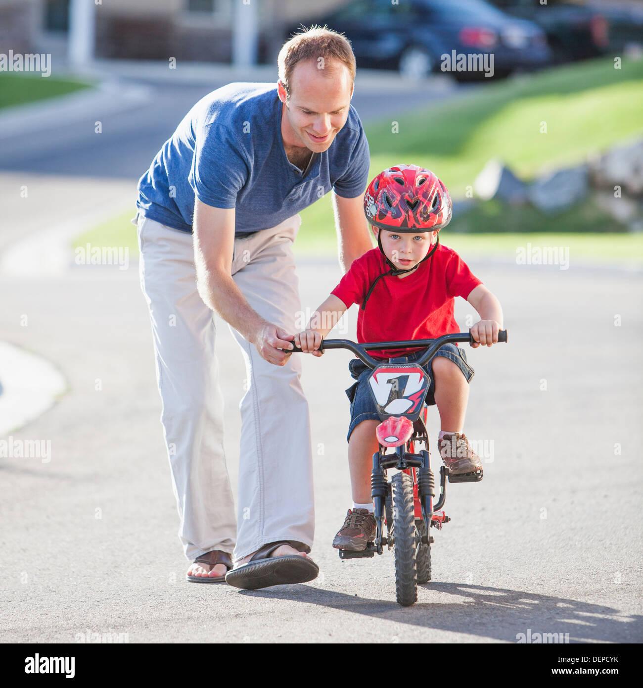 Hijo de padre caucásico enseñando a andar en bicicleta Foto de stock