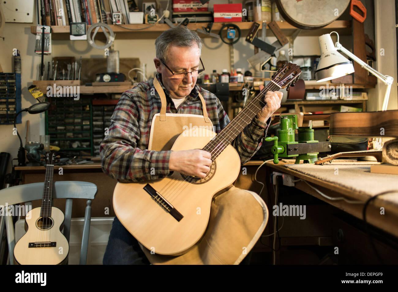 Guitarra maker la optimización y las pruebas de guitarra acústica en taller Imagen De Stock