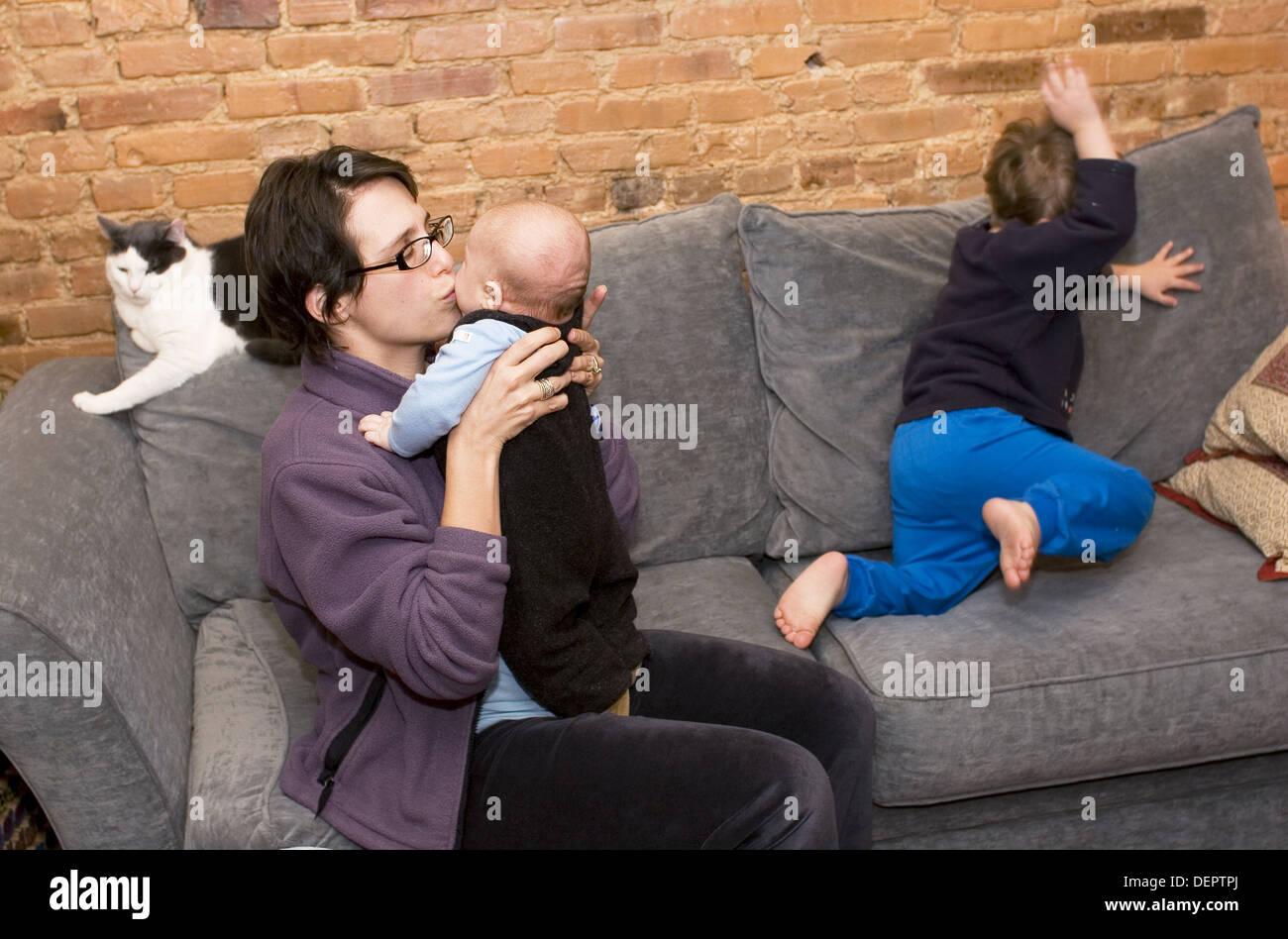 Madre con tres - año - viejo y tres - mes - viejo en el sofá con el gato mirando. Imagen De Stock