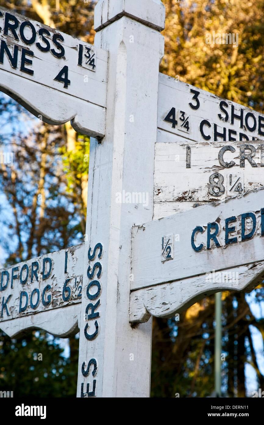 Cerca de la antigua dirección firmar en blanco y negro cerca de Crediton, Devon, Inglaterra Imagen De Stock