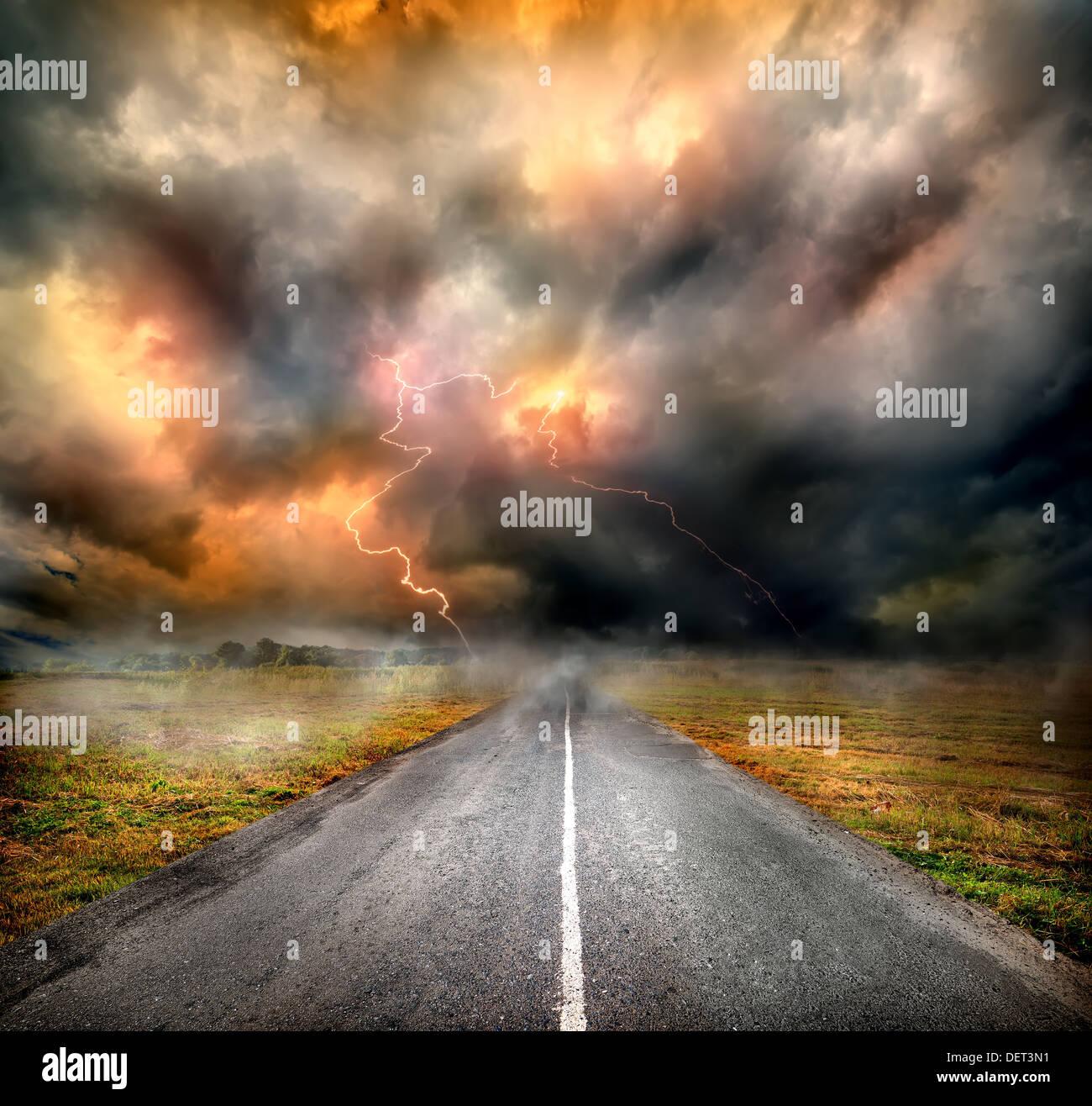 Nubes de tormenta y relámpago sobre la autopista en el campo Foto de stock