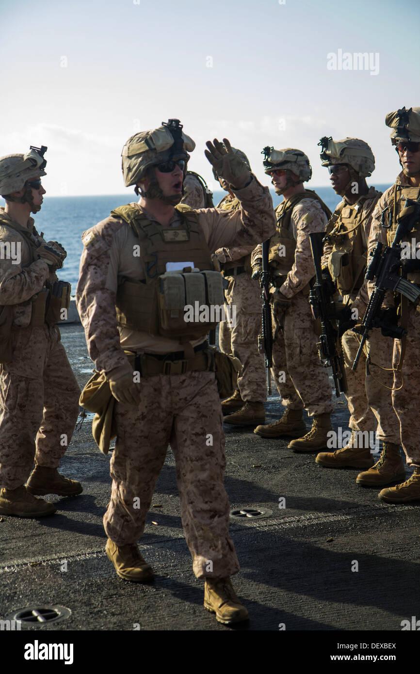 Los Marines de EE.UU. asignados a la compañía L del Batallón de equipo de aterrizaje 3/2, 26ª Unidad Expedicionaria de los Infantes de Marina (MEU), son informados sobre las iteraciones de destino durante un ejercicio de fuego vivo en la cubierta de vuelo del USS San Antonio (LPD 17), en el mar, del 12 de septiembre, 2013. La 26ª MEU es Foto de stock