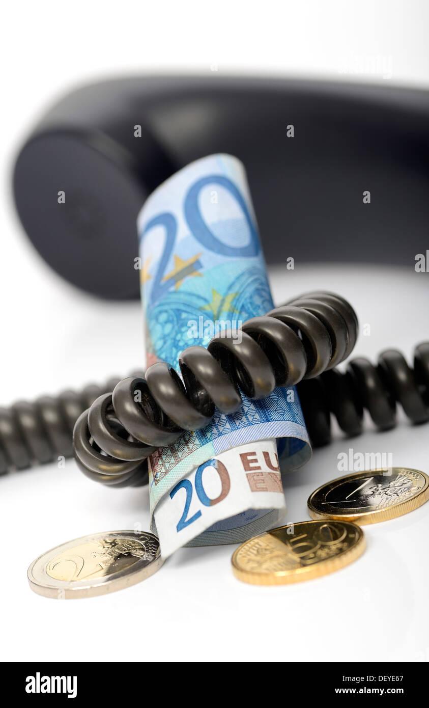 Teléfono con billetes de banco y monedas monetario simbólico, bucle de espera fotos responsable por los costos, Foto de stock