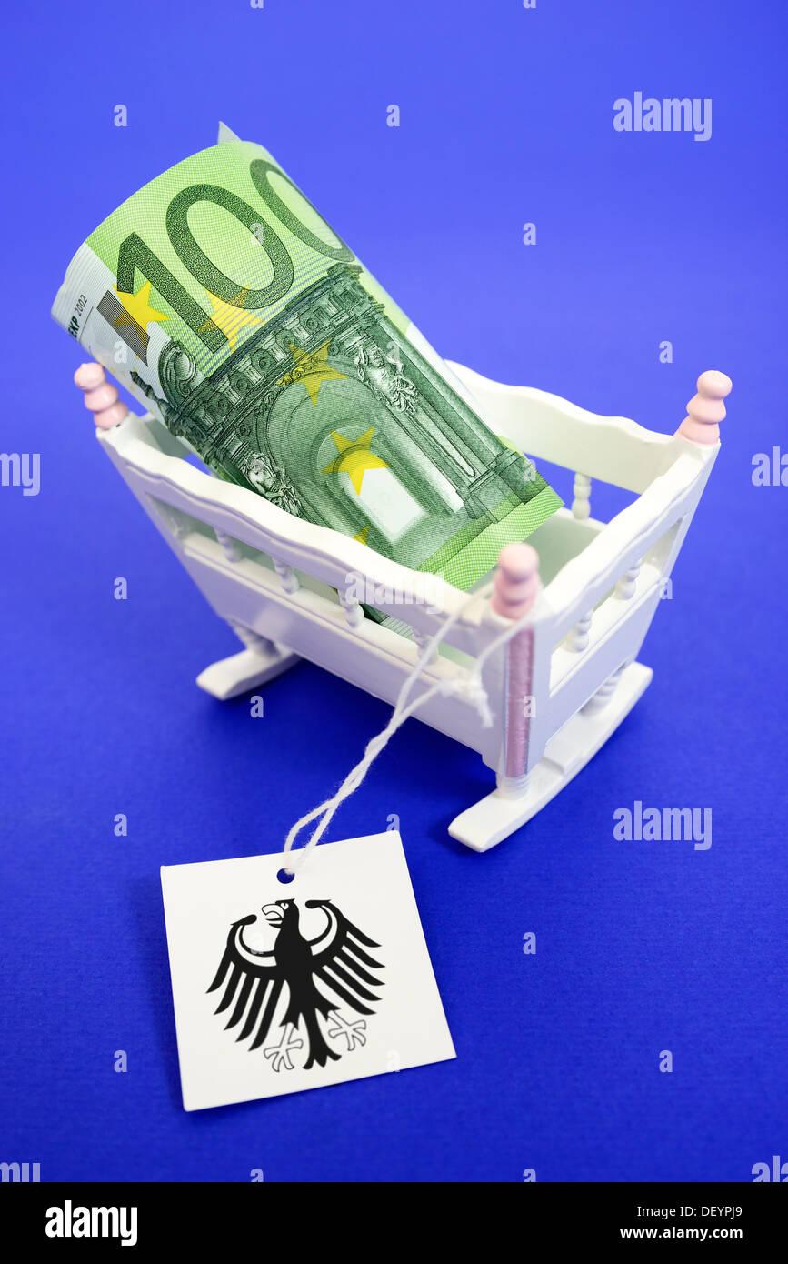 Cuna de niño con cien euros y etiqueta con el águila federal, los fondos para la atención de la foto simbólica, mit Kinderwiege Hundert-Euro-Schein und Imagen De Stock