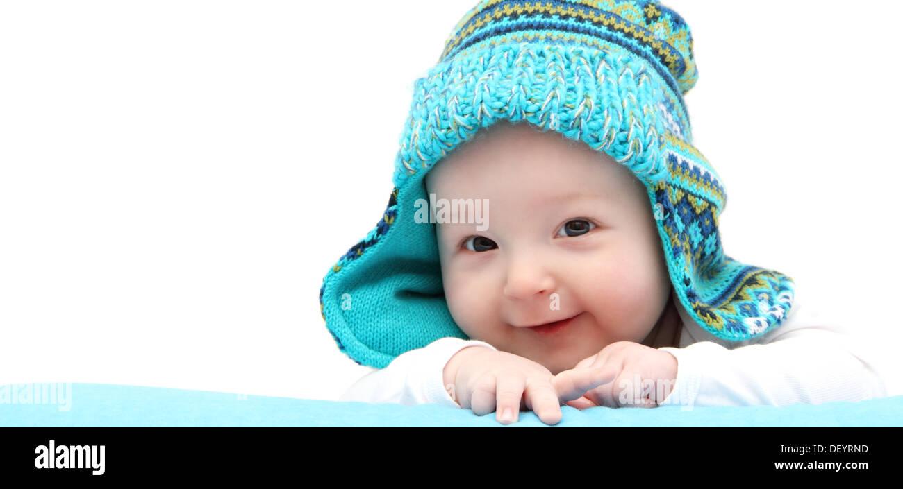 Happy Baby Boy en el gorro de punto sobre el estómago Imagen De Stock