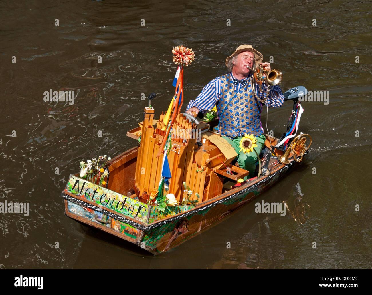 Un músico callejero ( Reinier Sijpkens ) tocando la trompeta en un órgano barco sobre un canal en Amsterdam, Imagen De Stock