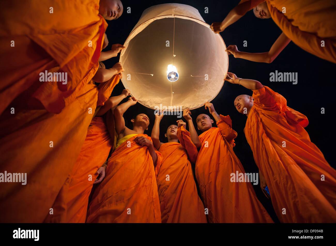 Los monjes liberando una linterna Kongming o cielo linterna para suerte durante el Loi Krathong Loy Gratong o Festival, Imagen De Stock