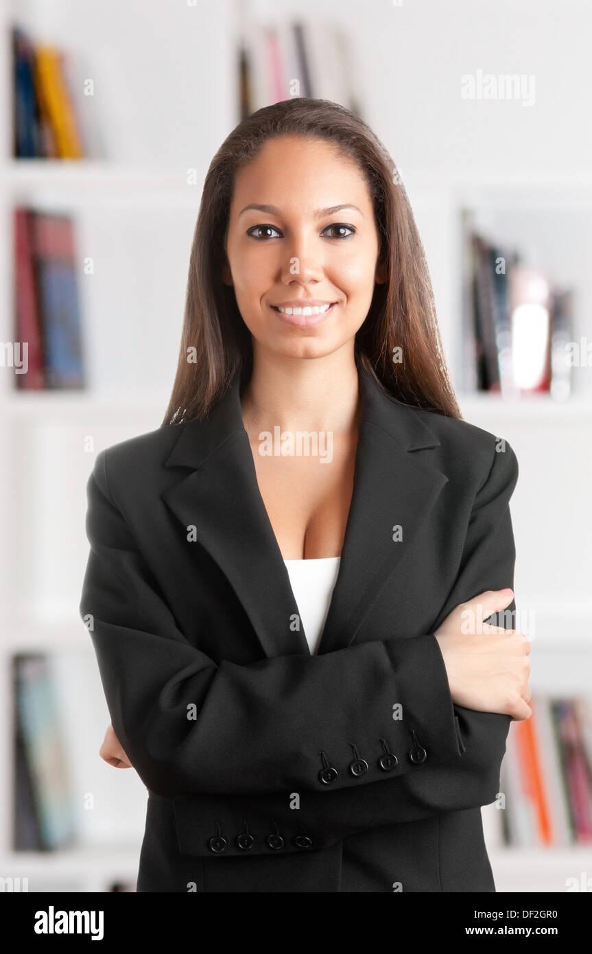 Retrato de una joven mujer de negocios africanos con sus brazos cruzados, sonriendo, en una oficina. Imagen De Stock