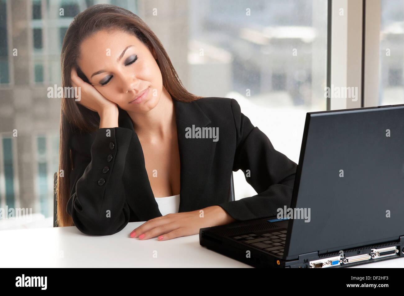 La empresaria estaba sentada en su pupitre cansada y soñolienta en una oficina. Imagen De Stock