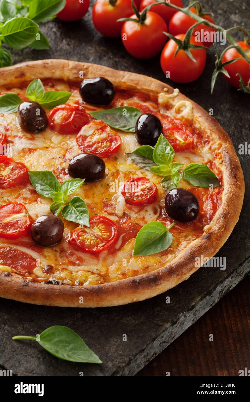 Pizza italiana de estilo rústico con mozzarella, queso y hojas de albahaca Imagen De Stock