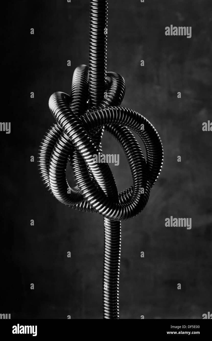 Imagen en blanco y negro de un negro enredado manguera flexible. Imagen De Stock