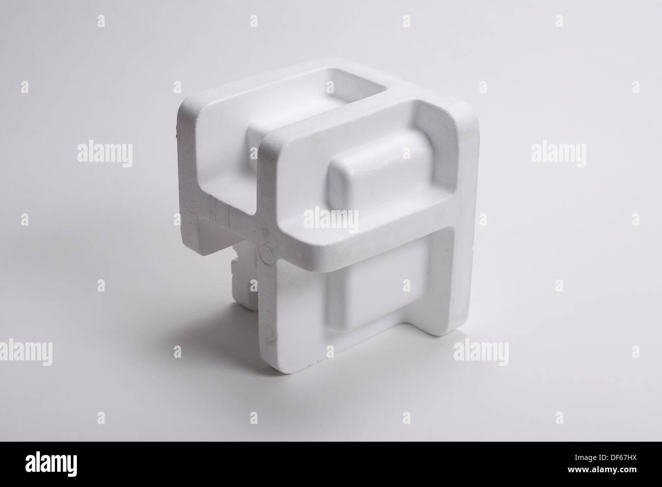 Pieza de poliestireno blanco formado como un trozo de material de embalaje. Imagen De Stock