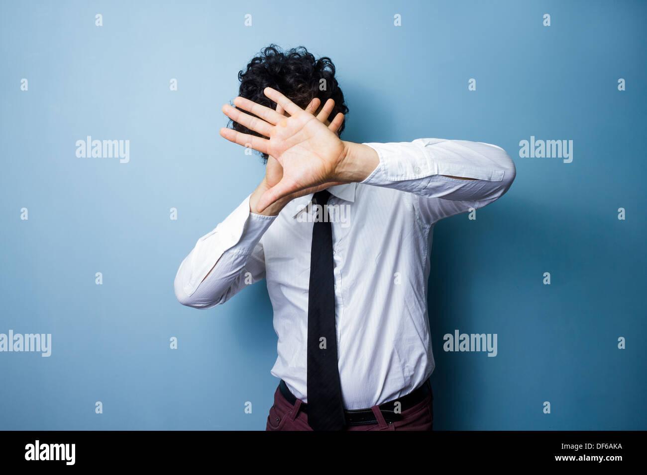 Joven está protegiendo su rostro forma luces cegadora. Imagen De Stock