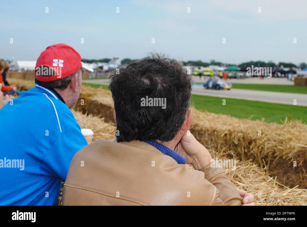 Los espectadores masculinos viendo el deporte de motor Imagen De Stock