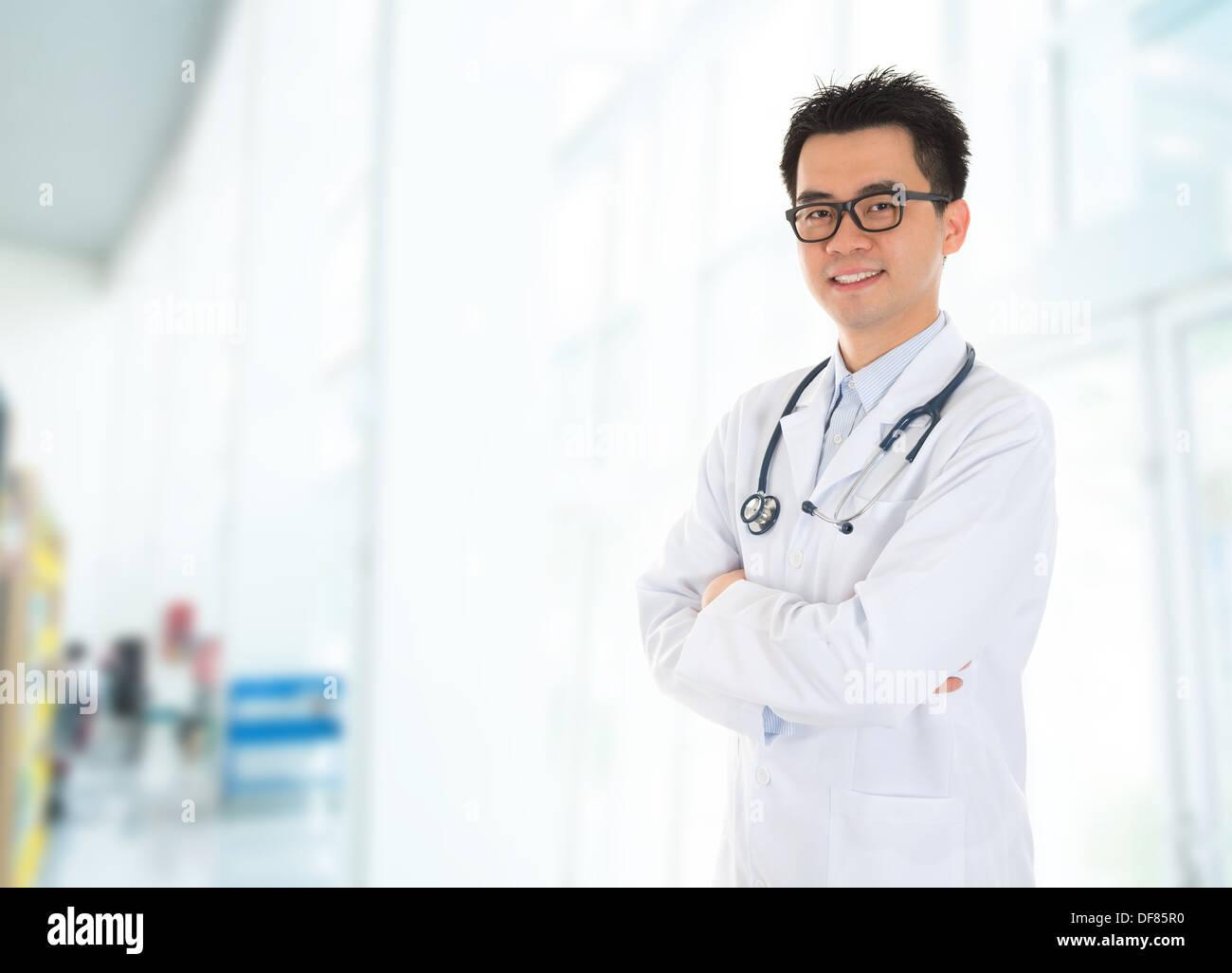 Médico masculino asiático con sonrisa segura de pie dentro del edificio del hospital. Imagen De Stock