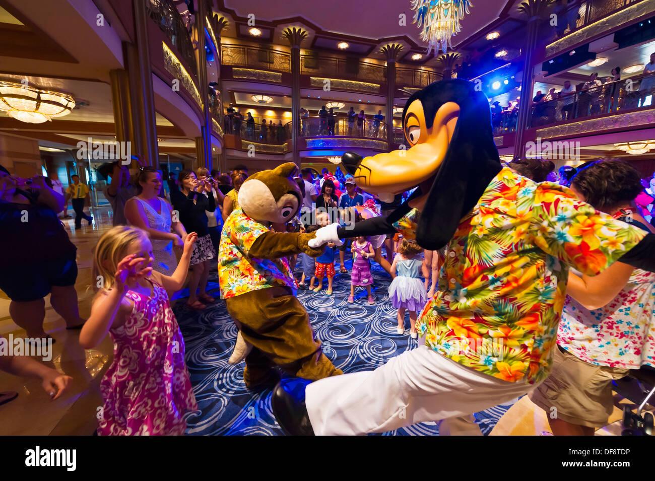 Goofy y Max GUF, carácter fiesta bailable, en el atrio del vestíbulo en el nuevo Disney Dream Cruise Ship navegando entre la Florida y Foto de stock