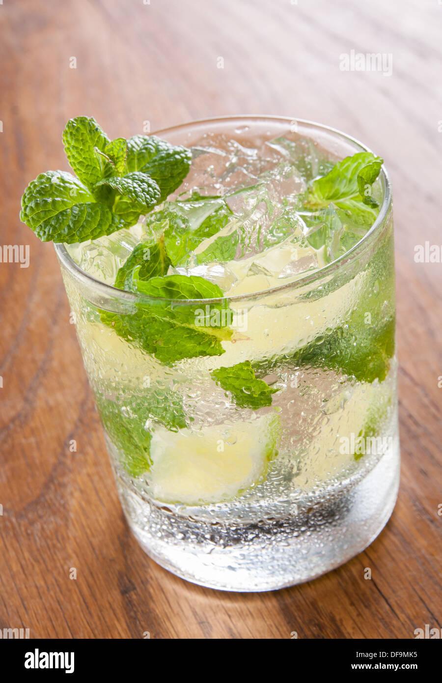Mojito sirve en un vaso con hielo picado y limón sobre mesa de madera Foto de stock
