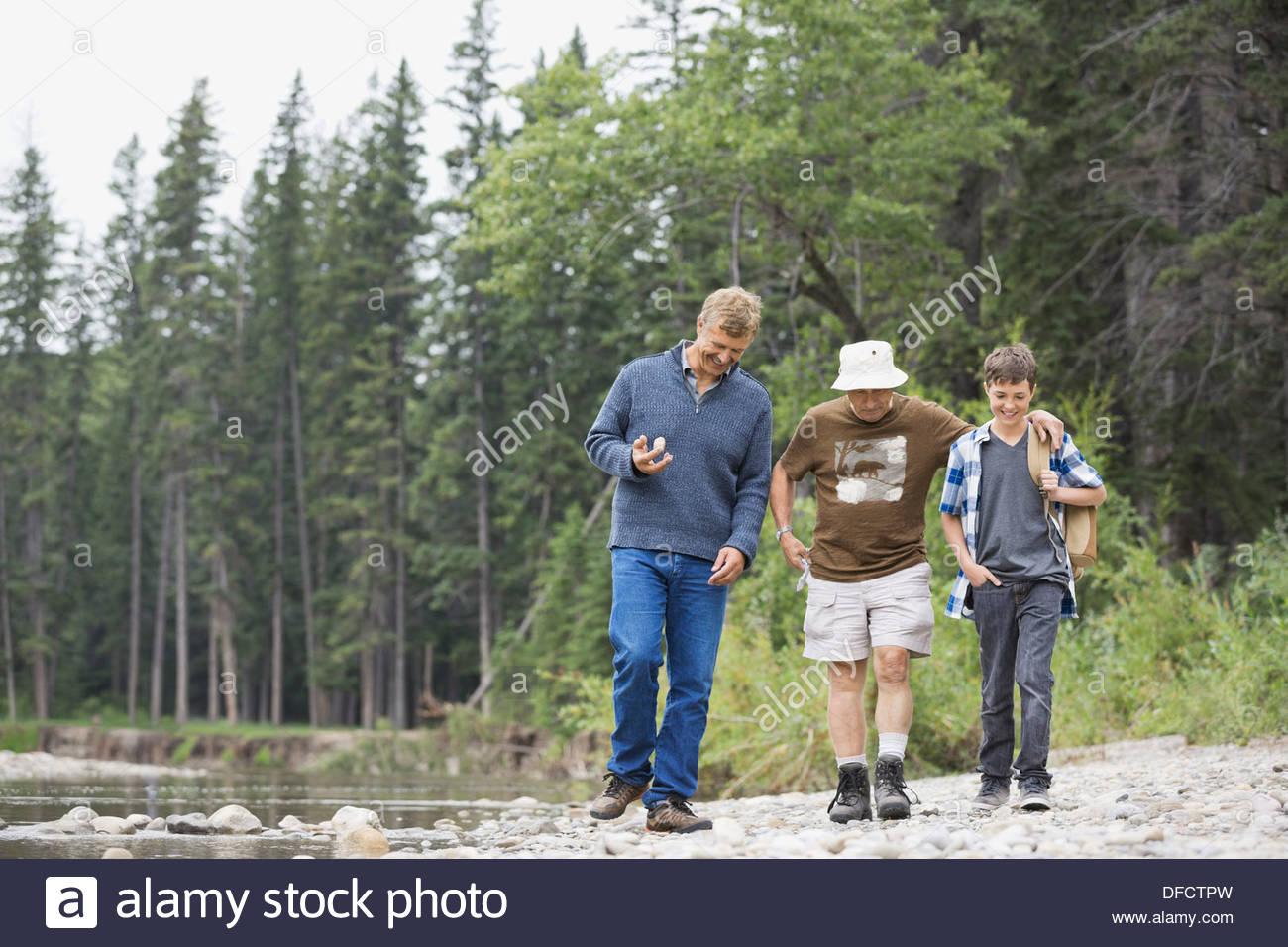 Generación de tres hombres caminando en el banco del río Imagen De Stock