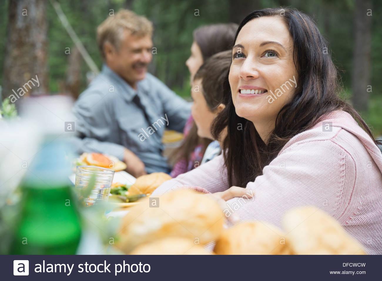 La mujer disfruta de comida con la familia en camping Imagen De Stock