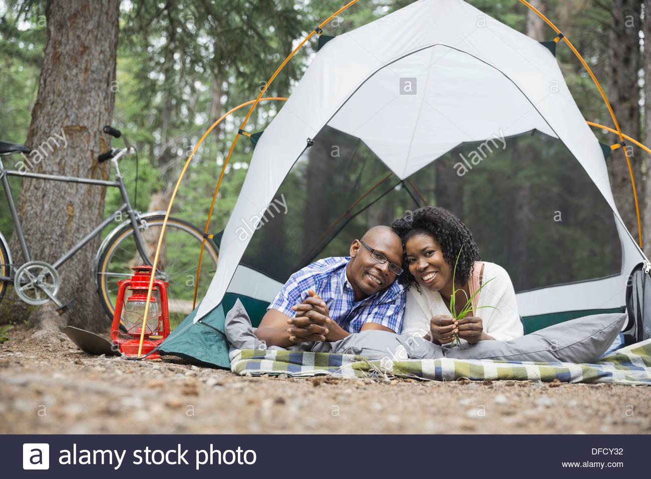Retrato de pareja feliz tumbado en la tienda en el camping Imagen De Stock