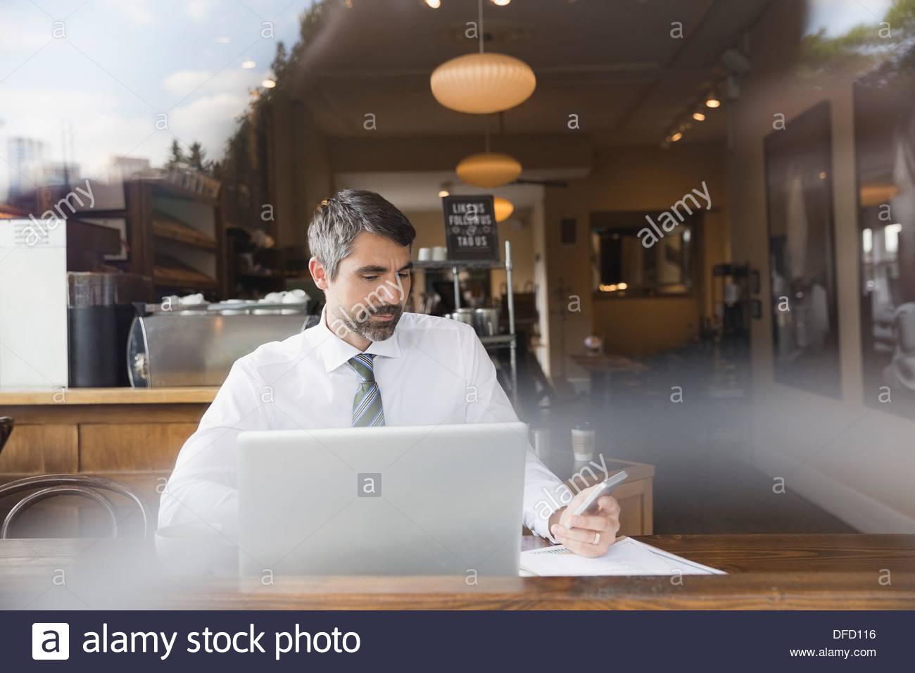 Empresario trabajando en dispositivos inalámbricos en un café Imagen De Stock
