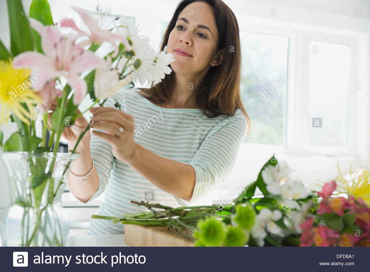 Mujer arreglar las flores en un jarrón en casa Imagen De Stock