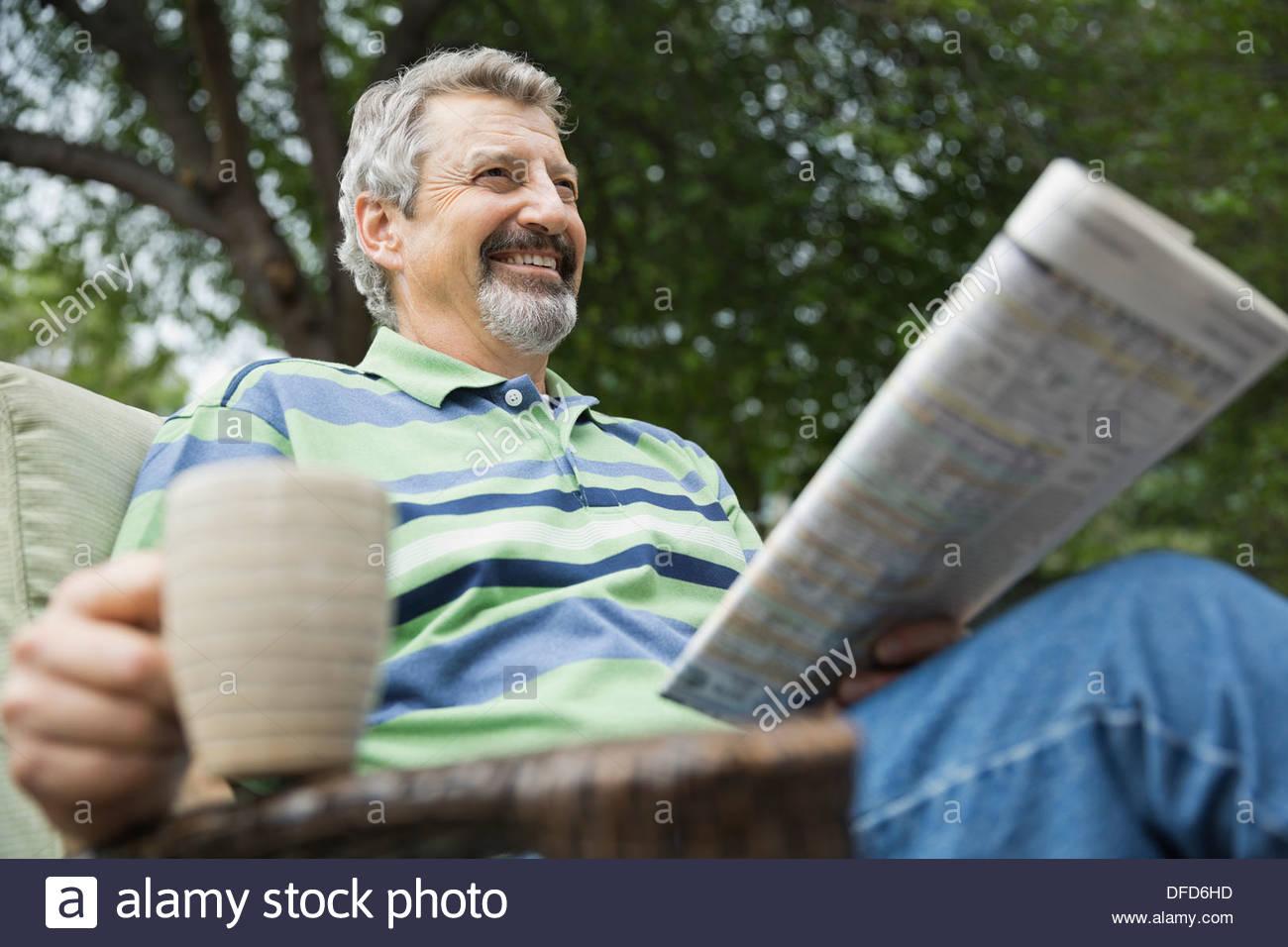 Feliz senior hombre con taza de café y un periódico sentado en el patio Imagen De Stock