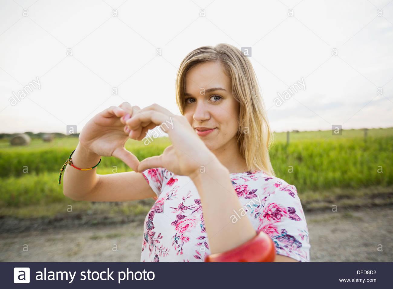 Retrato de mujer hermosa haciendo corazón firmar con las manos Imagen De Stock