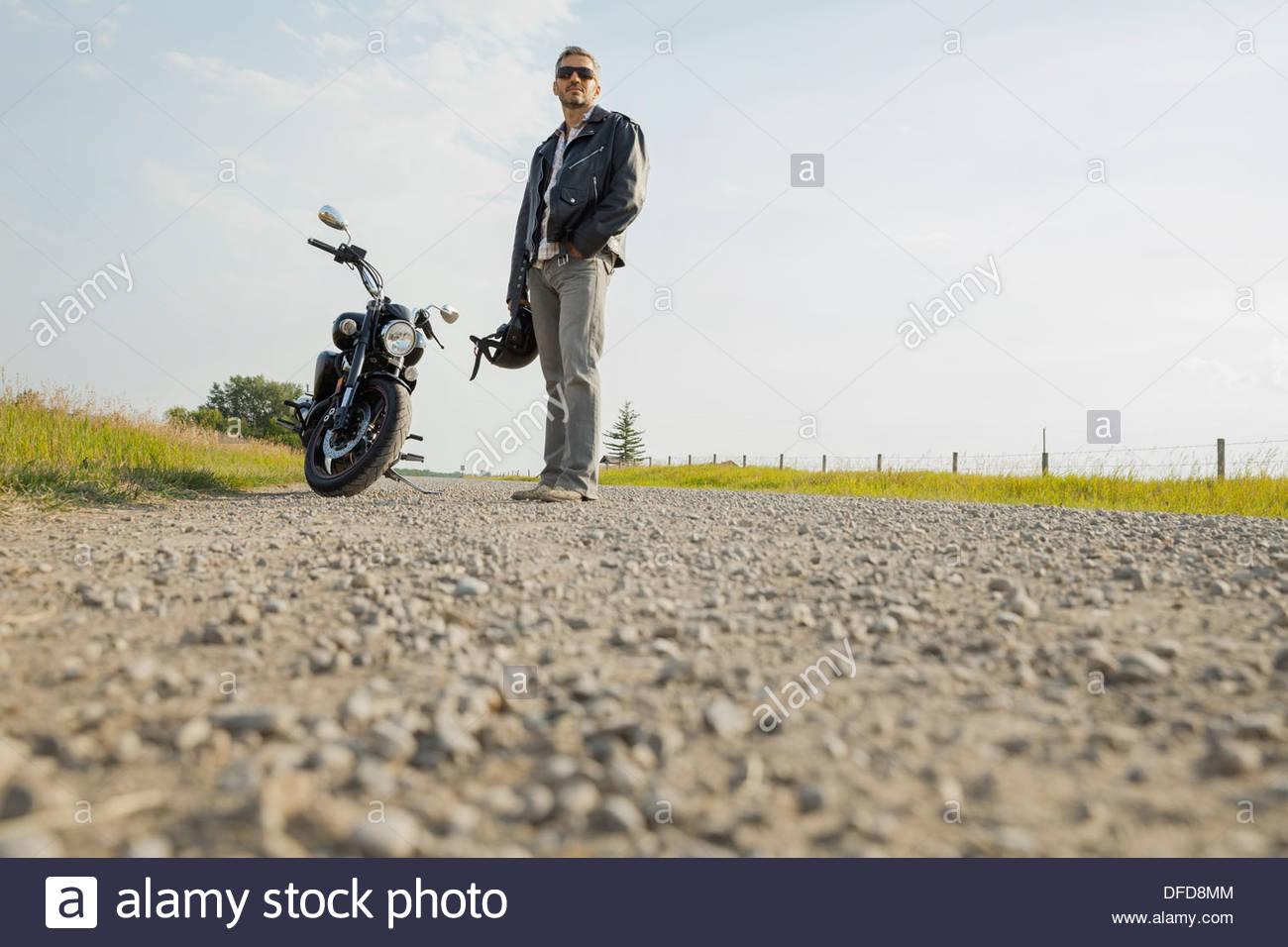 Hombre con su moto, tomando un descanso en un país por carretera Foto de stock