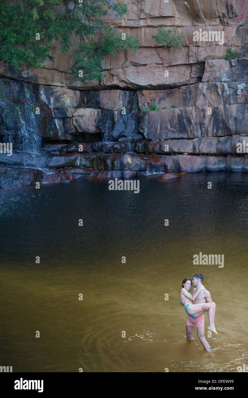 El hombre lleva la novia en la piscina Imagen De Stock