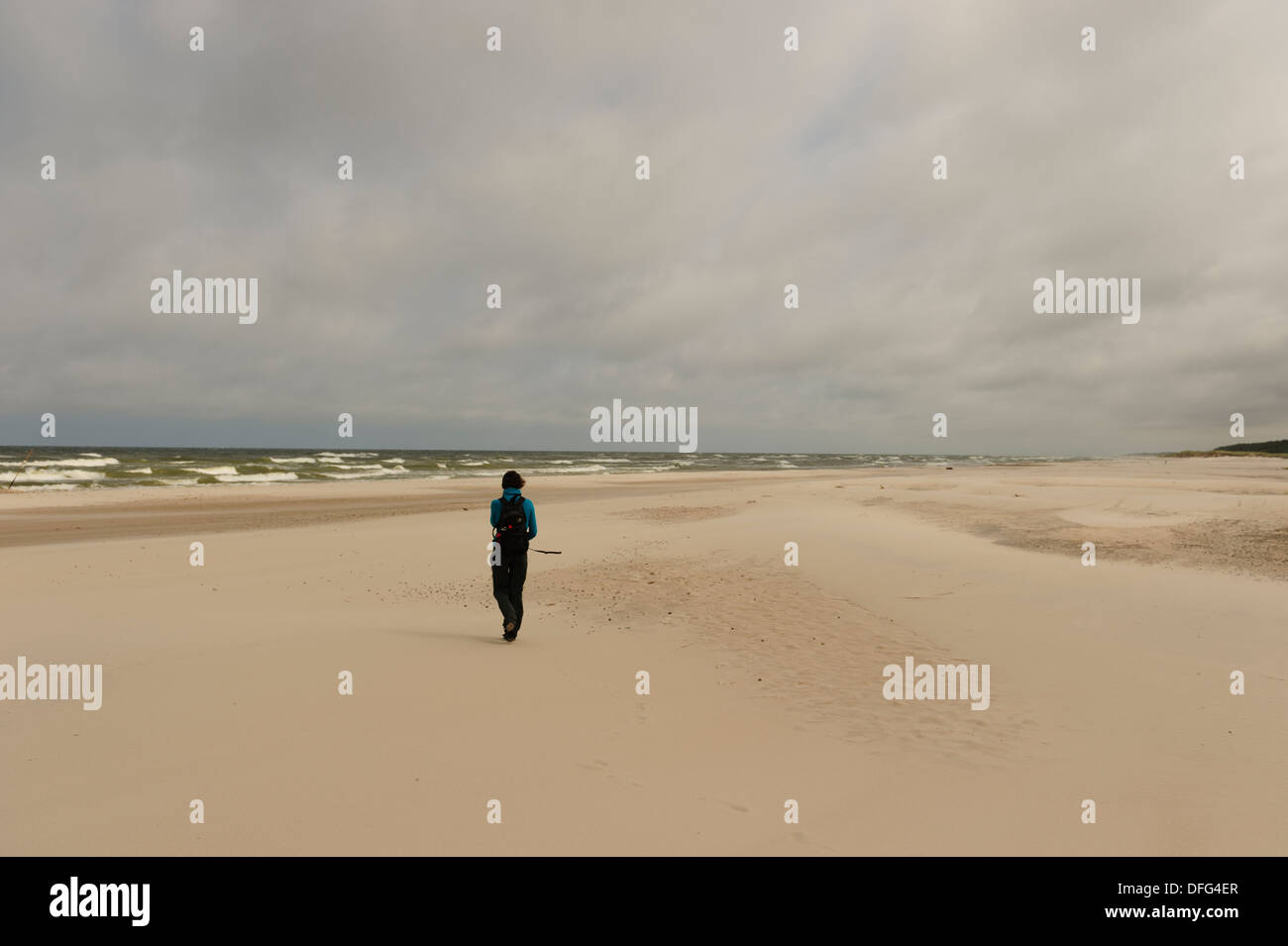 Una mujer camina por la playa de arena blanca del Parque Nacional Slowinski, en Polonia. Foto de stock