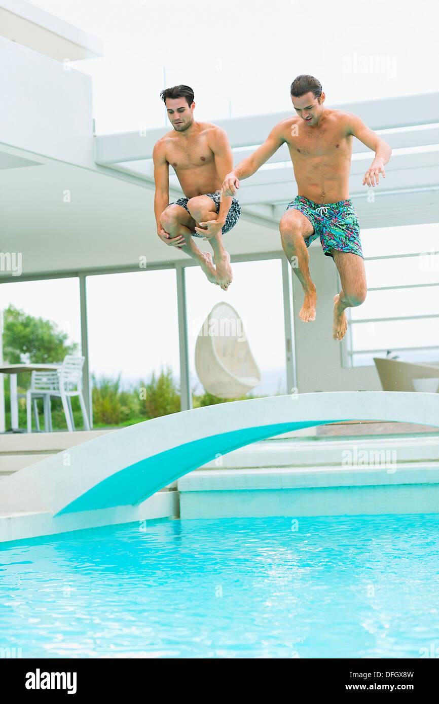 Los hombres saltando a la piscina Imagen De Stock