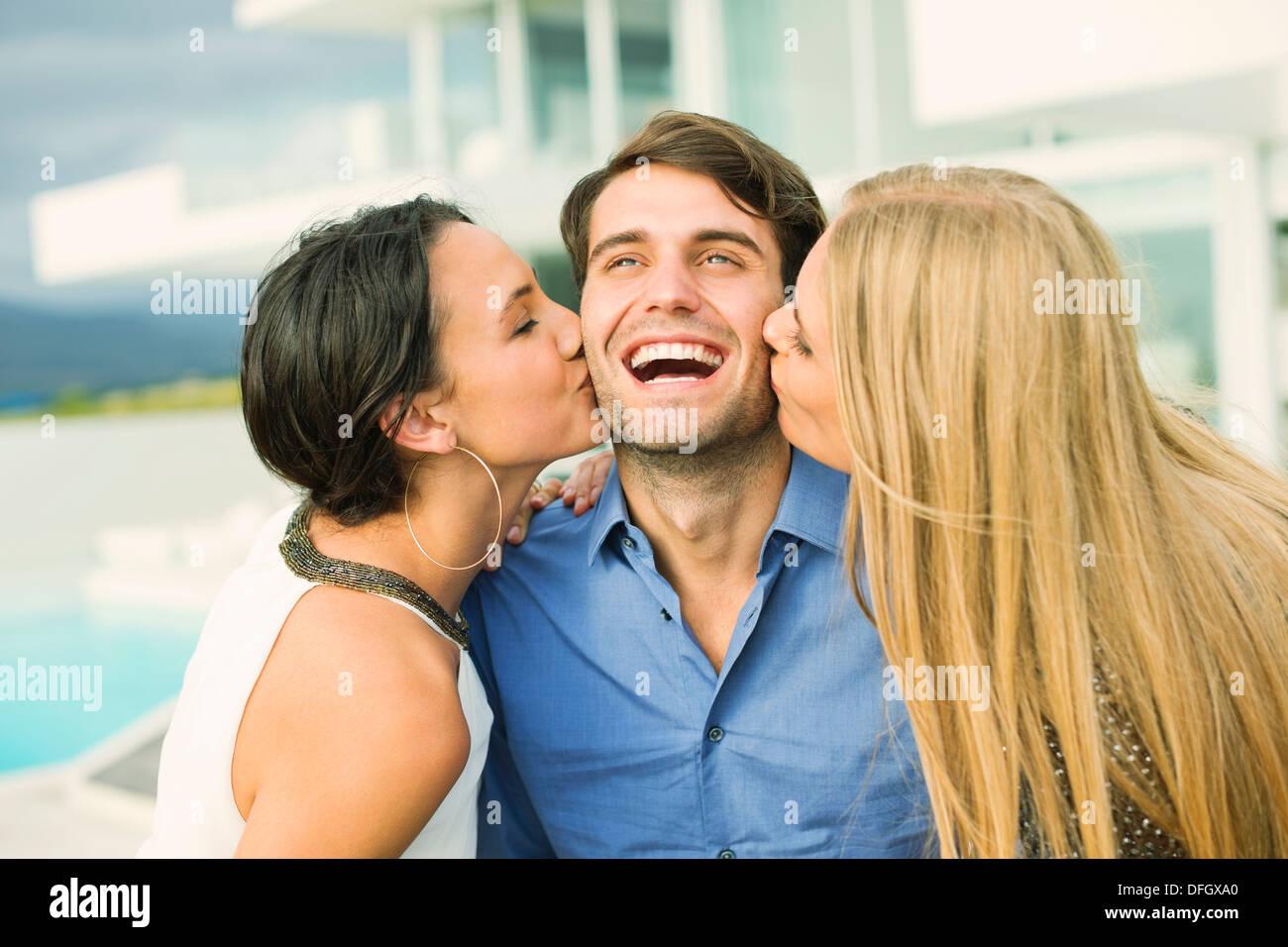 Las mujeres besar la mejilla del hombre al aire libre Imagen De Stock