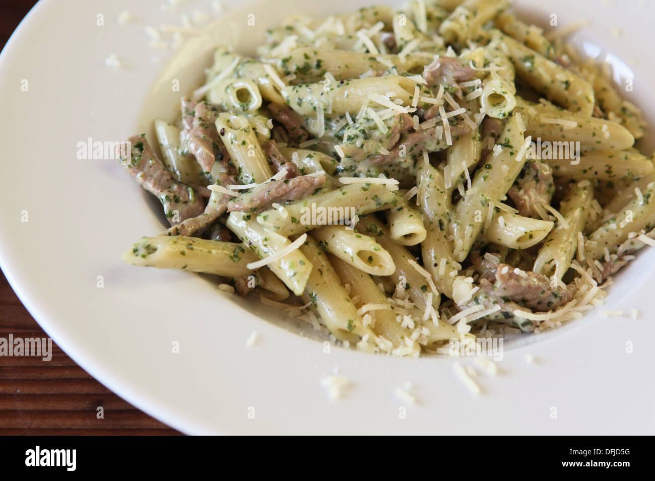 Una porción de pasta penne con hierbas, carne y queso Imagen De Stock