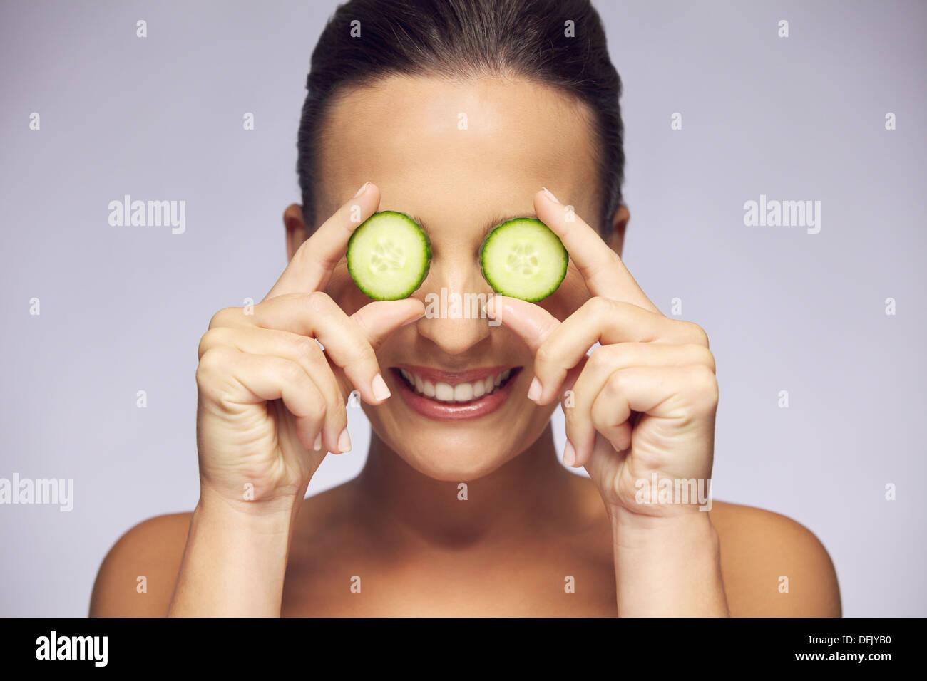 Hermosa y sonriente joven mujer sosteniendo la rebanada de pepino en frente de los ojos sobre fondo gris. Concepto de cuidado de los ojos Imagen De Stock