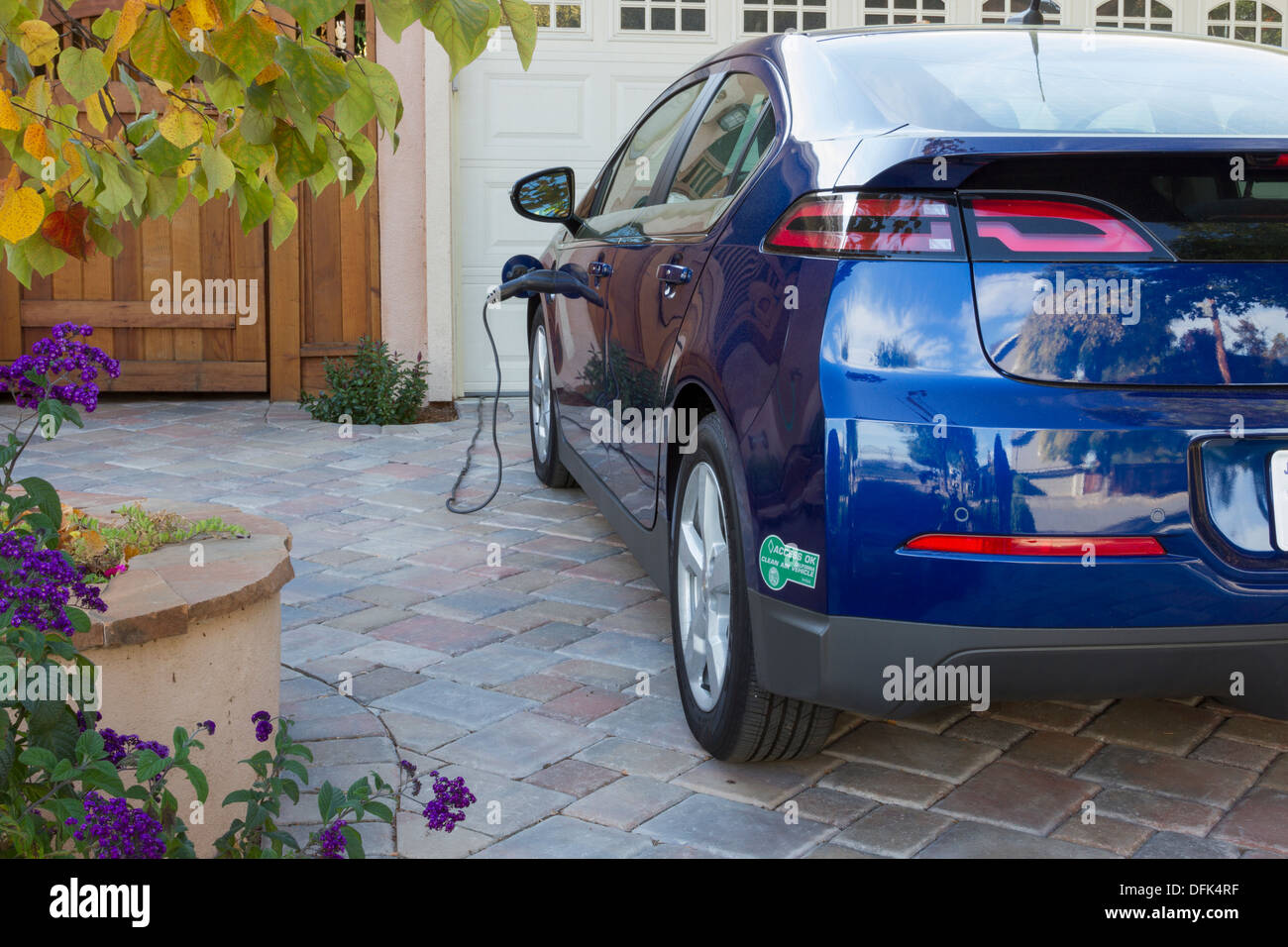 Plug-in coche eléctrico con carpool sticker estacionado en la cochera, con el conector enchufado y cargando Imagen De Stock