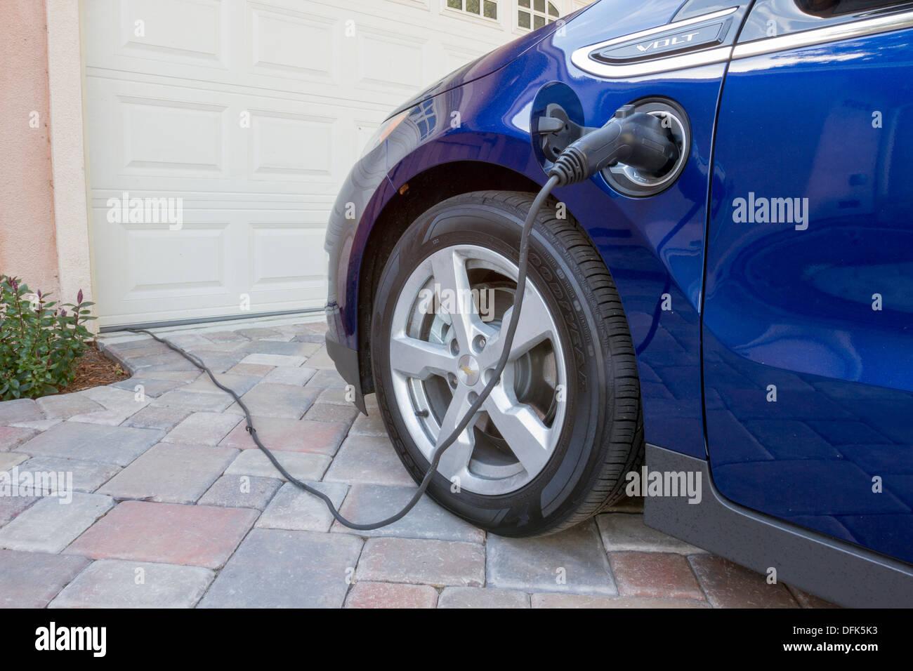 Chevrolet Volt plug-in coche eléctrico con el conector enchufado en la carga, en casa, en un camino de entrada Imagen De Stock