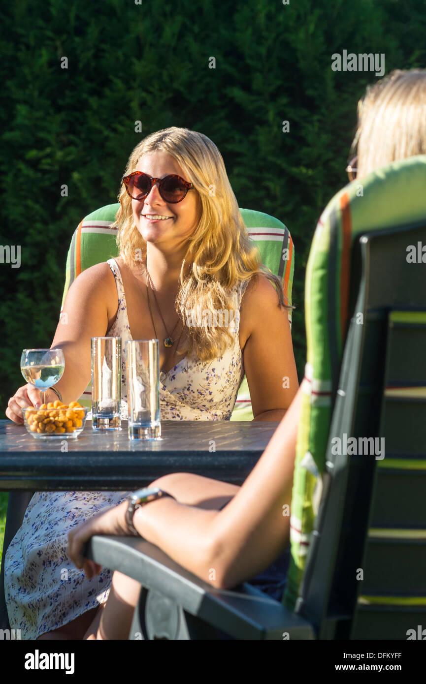 Dos mujeres jóvenes disfrutando de bebidas fuera en una tarde soleada Imagen De Stock